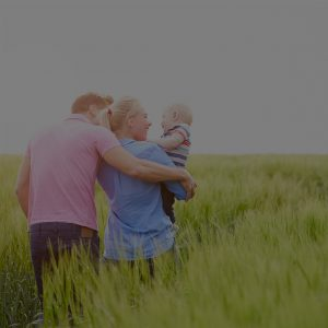 Family Walking Through Field of Green Grass
